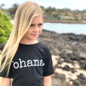 blonde girl standing on the rocks by the ocean wearing a black 'ohana tshirt