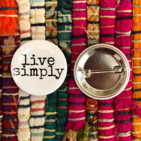 live simply on a campaign pin on a colorful rug