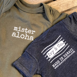 olive green and  navy blue baby boy Ivy & Co. onesie with white lettering that says mister aloha