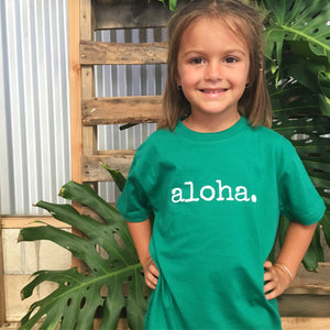 girl with hands on hips in front of monstera leaves wearing a green tshirt that says aloha