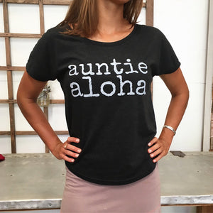 woman wearing a black auntie aloha scoop neck tshirt with pink skirt
