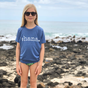 blonde girl standing on the rocks by the ocean wearing sunglasses wearing a blue 'ohana tshirt