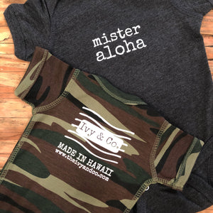 dark grey and camouflage baby boy Ivy & Co. onesie with white lettering that says mister aloha