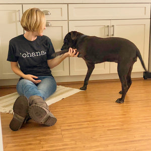 Girl sitting on the floor in boots and a tshirt that says 'ohana petting her brown dog