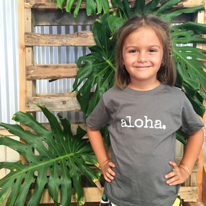 girl with hands on hips in front of monstera leaves wearing a grey tshirt that says aloha