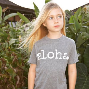 blonde girl standing in front of Hawaiian foliage wearing a grey tshirt that says aloha