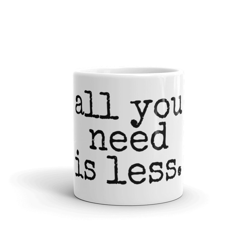 white mug with black font that says all you need is less