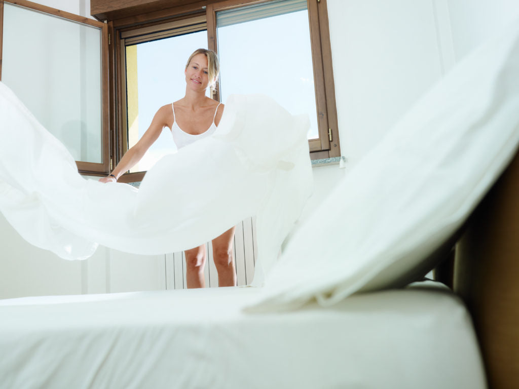 """mid adult woman making bed with white sheet. Horizontal shape, low angle view"""