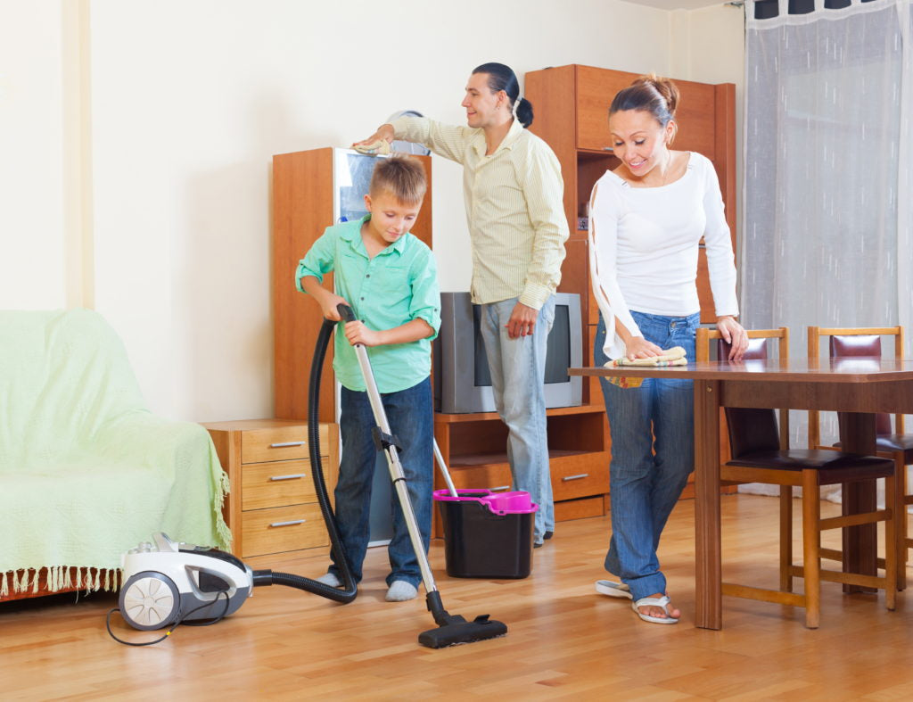 Ordinary family of three doing housework together in home