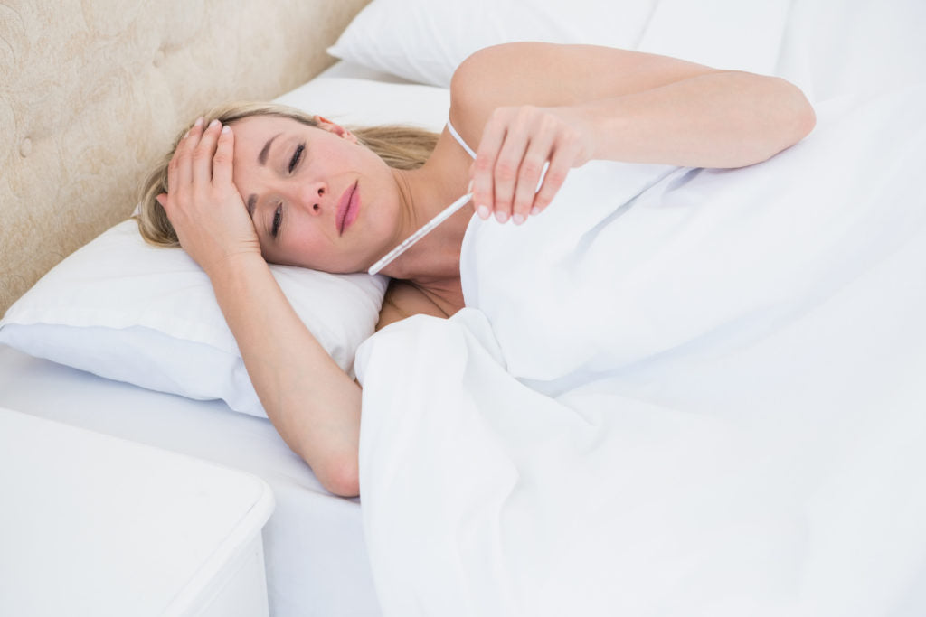 Blonde woman checking her temperature at home in the bedroom