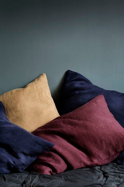 pillows and shams in moody, dark blue, yellow and red casually on a bed with dark gray sheets, wall in gray green.