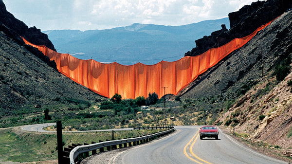 a red car on a road leading to the mountains, an orange fabric wall by Christo and Jeanne-Claude in valley.