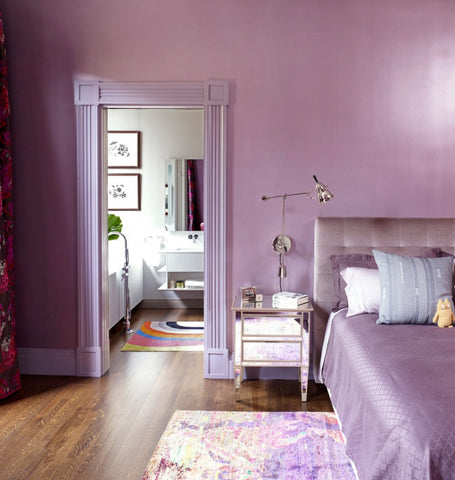 a beautiful bedroom in purple - wall, door, nightstand, headboard, and bedding.