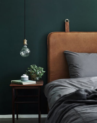 a modern, industrial bedroom with dark green walls, leather headboard and bedding in gray. A fit for men's bedrooms. change the sheets.