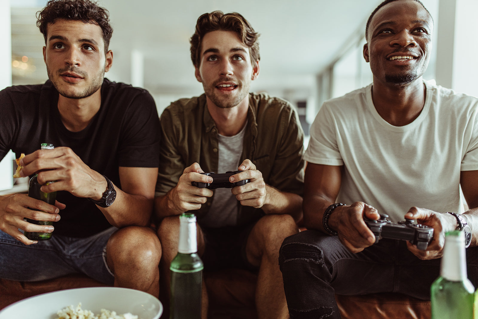Men with different skin types, black, white, asian skin types playing video games while showing skin and skincare problems in the world for mens skincare.
