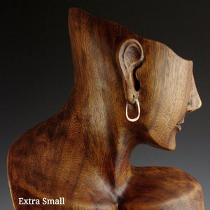 Extra small copper elliptical hoop earrings on model