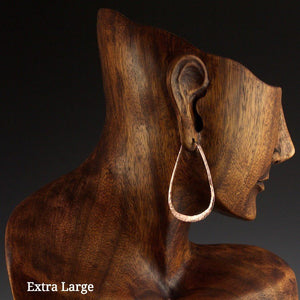 Extra large copper elliptical hoop earrings on model