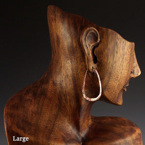 Large copper elliptical hoop earrings on model