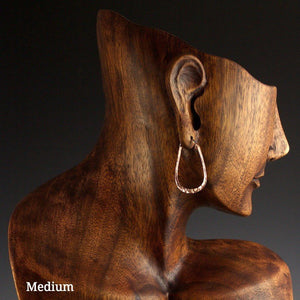 Medium copper elliptical hoop earrings on model