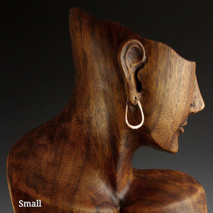 Small copper elliptical hoop earrings on model