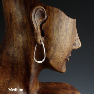 Medium sterling silver elliptical hoop earrings on model