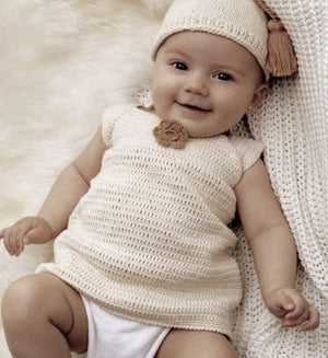baby wearing a ALPACA BABY POM POM HAT BEIGE AND ALPACA DRESS  handmade of 100% Peruvian alpaca wool