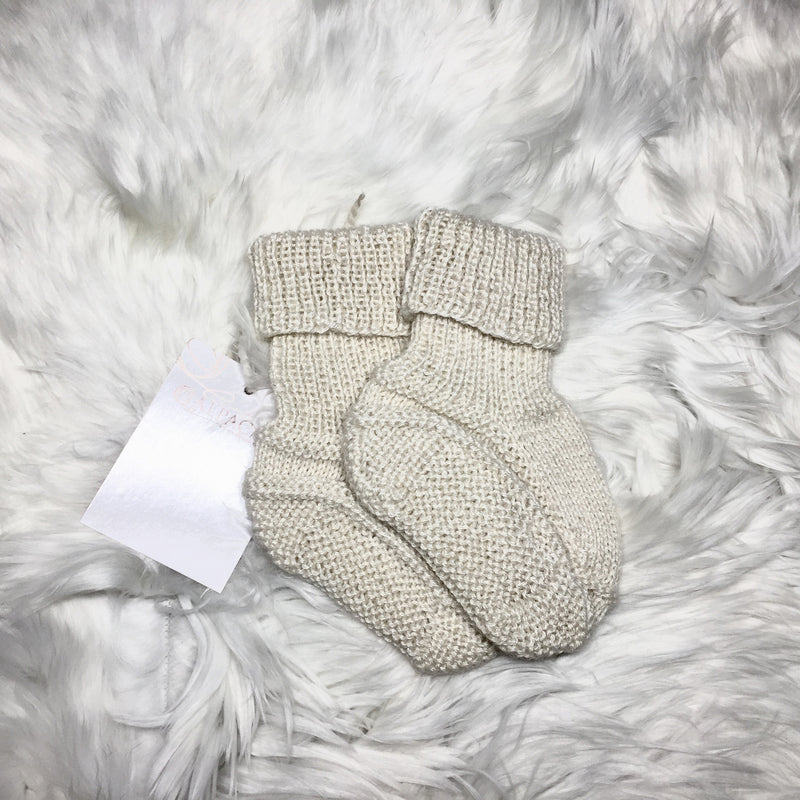 Leg of a  baby with ALPACA BABY KNITTED SHOES BEIGE handmade of 100% Peruvian alpaca wool