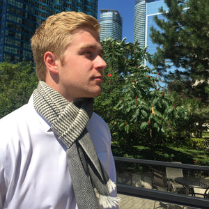 Young man with Black and white scarf with little squares and andine design handmade of 100% Peruvian alpaca wool