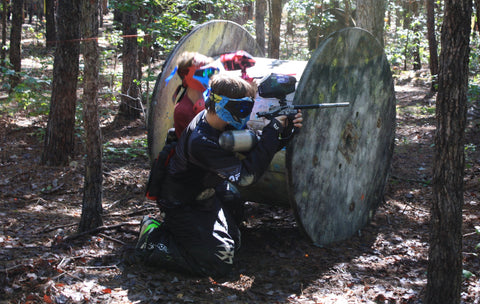 paintballer using a big spool for cover during an intense paintball match right outside of charlotte north carolina