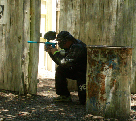 man crouched next to barrel shooting his marker at boss paintball