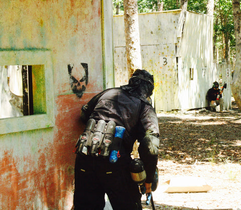 red teamate checking around a corner at the school house in george town at boss paintball fields