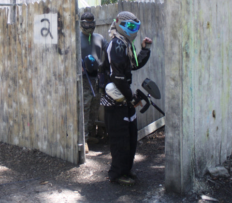 guy standing outside of a building during an intense paintball scenario while aiming his gun at the ground