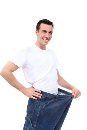 Happy man stretching out pants waist line to emphasize weight loss