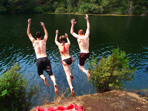 Three people jumping off ledge into a lake