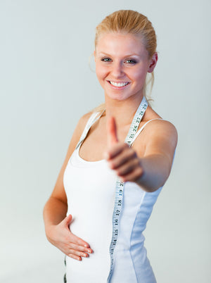 Happy fit lady with thumbs up and measuring tape