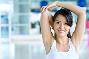 Woman smiling while stretching her triceps