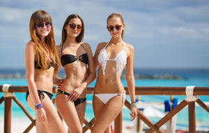 Three slim woman in bikinis smiling at camera