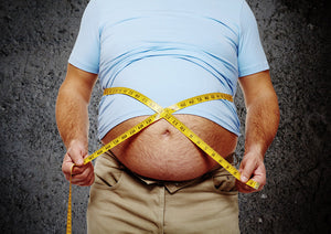Overweight man with measuring tape stretched around belly