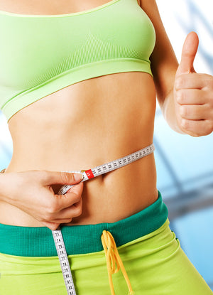 Slim woman with thumbs up while holding measuring tape around slim waist