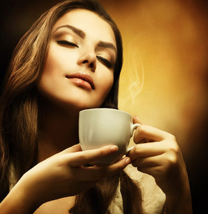 Woman smelling cup of coffee