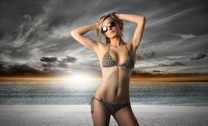 Slim woman posing for camera with beach background