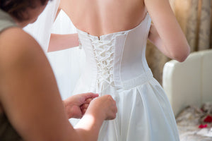 Bride having her gown's corset tightened