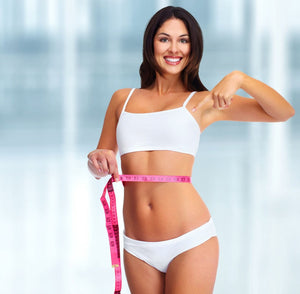 Woman Smiling while pointing down at measuring tape wrapped around slim waist