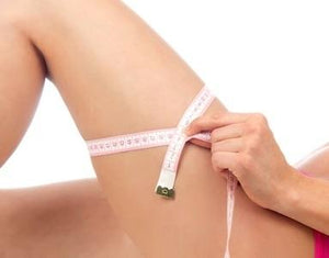 Woman with measuring tape wrapped around smooth thigh