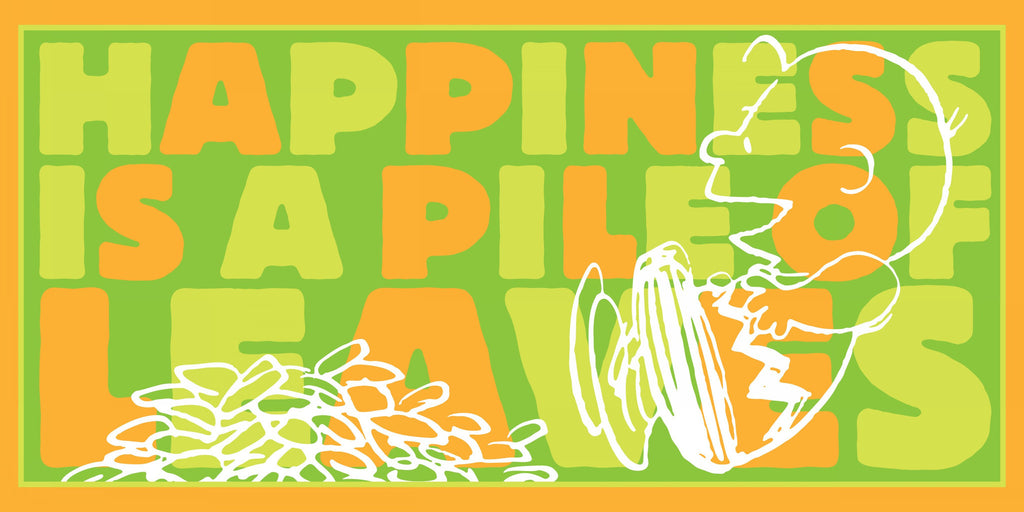 Charlie Brown jumps into leaves withe the words happiness is a pile of leaves