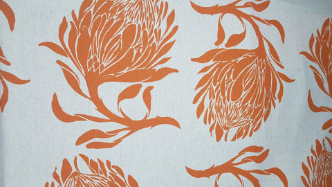 Stowe & so Table Cloth. 2m King Protea in Burnt Orange on Stone.