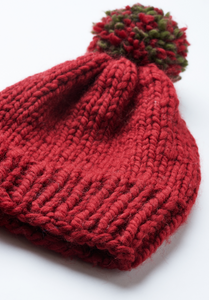 Hand knitted red beanie with red and green pompom