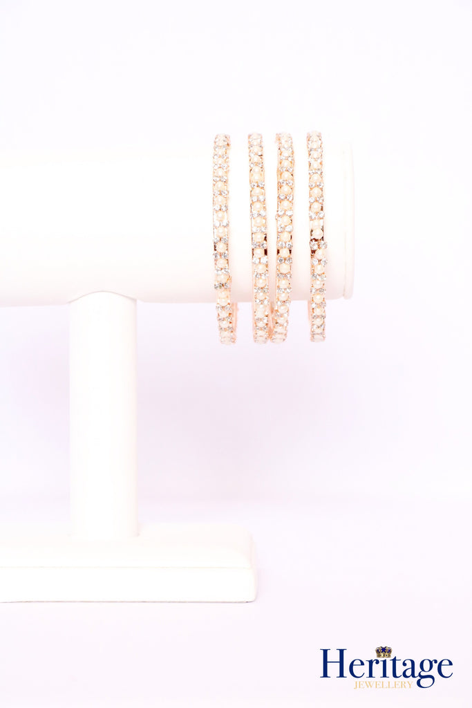 Rose gold bangles adorned with silver crystals.