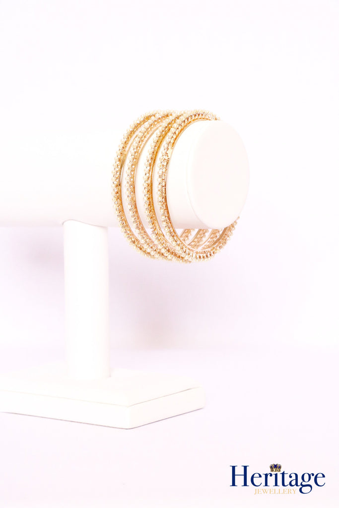 Rose gold bangles adorned with silver crystals and pearls.