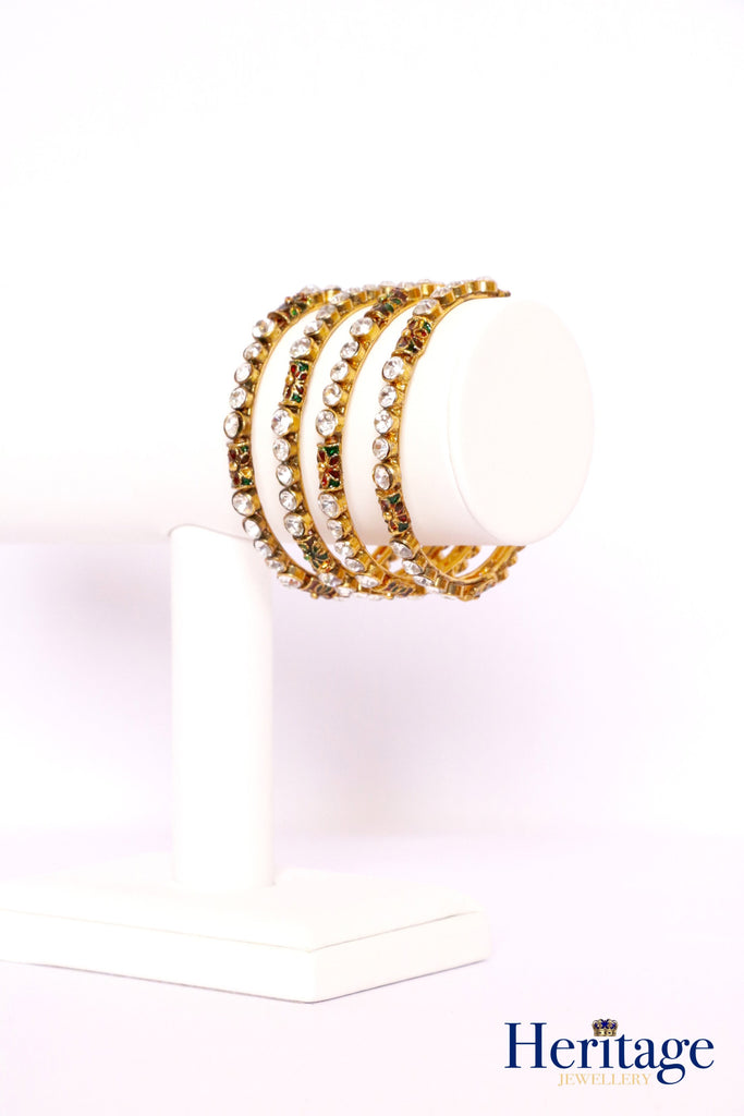 Antique gold kundan style bangles adorned with silver crystals.